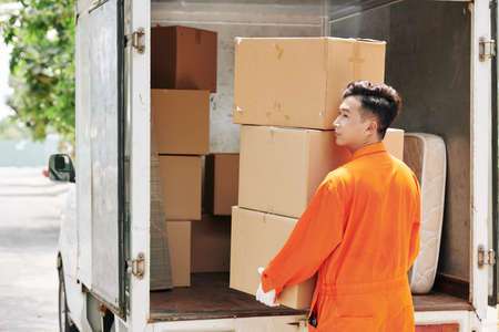 Asian young man carrying stack of cardboard boxes to truck trunk