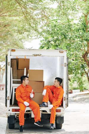 Déménageurs fatigués assis dans un coffre de fourgon chargé, buvant de l'eau et parlant pendant une courte pause