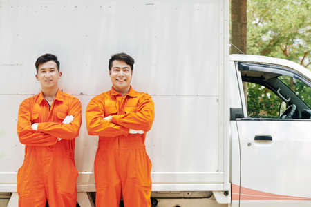 Positive confident Asian movers in orange uniform standing in front of van with arms crossed and smiling at camera