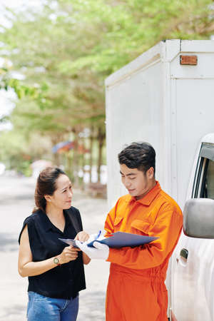 Moving service worker talking to female client and filling document with delivery details