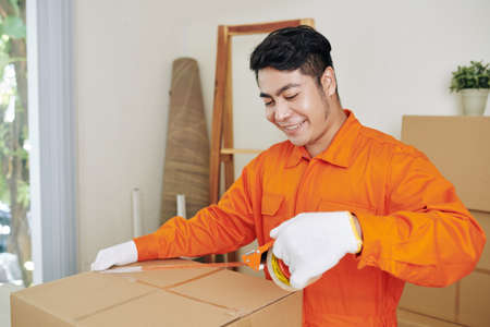Smiling positive Vietnamese moving service worker using adhesive tape to seal boxes with belongings