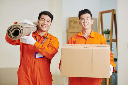 Positive moving service workers carrying rolled carpet and cardboard box