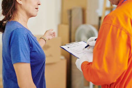 Mature female customer talking to mover who is filling details in delivery service document