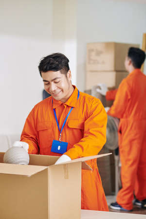Smiling Vietnamese moving service worker packing fragile objects in cardboard boxes