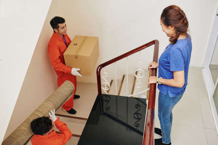Smiling mature woman looking at movers carrying her belongings in new apartment