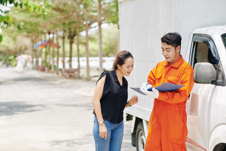 Moving service worker standing at van and writing down requests of female client