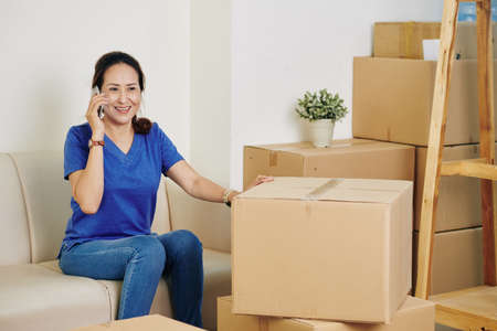Smiling mature Asian woman calling to moving service company after packing her belongings in cardboard boxes