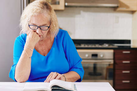 Senior woman sitting at kitchen table and reading captivating book