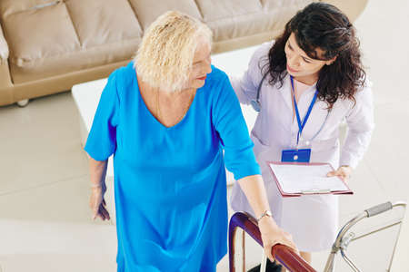 Smiling young doctor with clipboard helping senior woman to walk up the stairs
