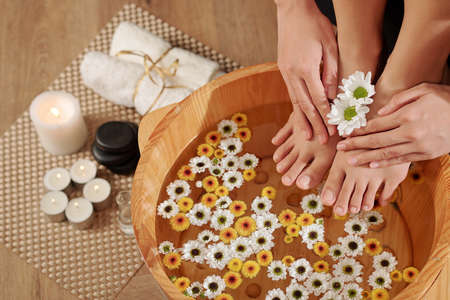 Woman putting feet in wooden basin with water and small flowers for making pedicure