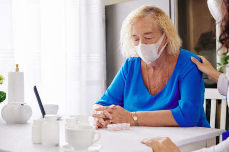 Doctor reassuring sad senior woman in medical mask after telling her diagnosis