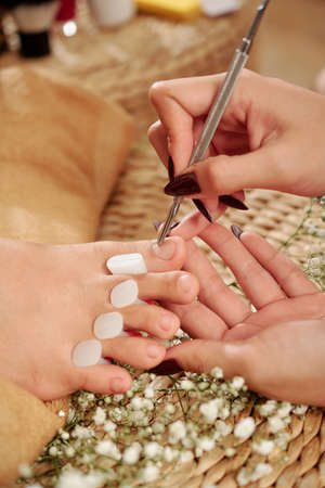 Close-up image of pedicurist using metal pusher to push cuticle from toenails