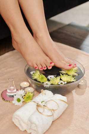 Woman putting feet in bowl with water, flowers and basalt stones