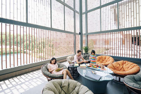 Parents with little daugher spending time in hotel lounge area