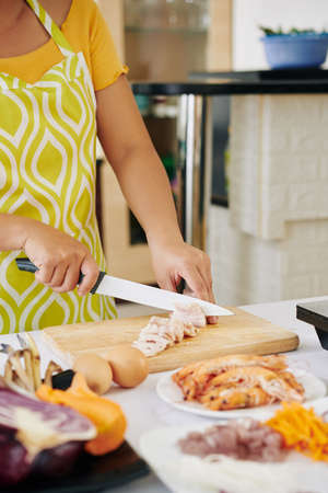 Close-up image of woman cutting bacon in thin slices when cooking breakfast