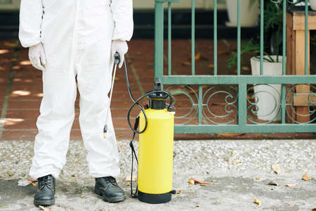 Cropped image of technician in protective coverall spraying activities to prevent spread of corona virus in the streets