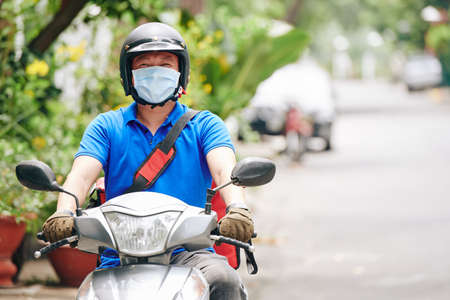 Courier in helmet and medical mask riding on scooter when delivering food to customers staying home during pandemic
