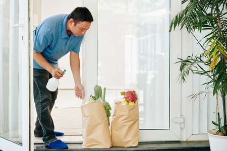 Mature Asian man opening entrance door and spraying delivered grocery packages with disinfecting spay