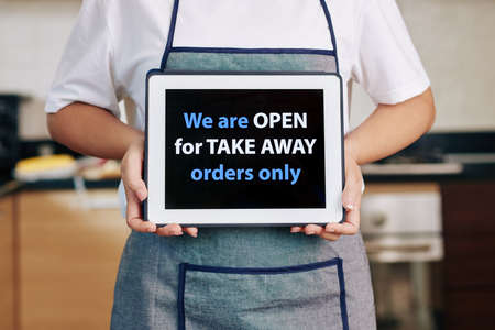 Cafe owner holding tablet computer with inscription explaining that they are working for take away orders only
