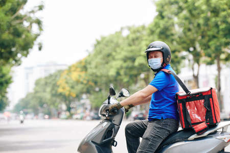 Cheerful courier riding on scooter when delivering food to customers during pandemic period Stock Photo