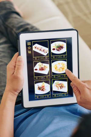Man with tablet computer choosing dishes from application of restaurant to order delivery