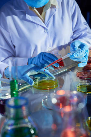 Close-up image of laboratory technicians putting reagents in petri dishes with colorful liquids