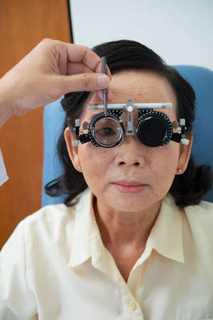 Senior Vietnamese woman having her eyes examined at ophthalmology clinic