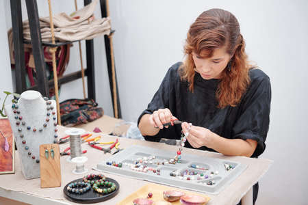 Young woman concentrated on making jewelry and using pliers to attach hook Banque d'images
