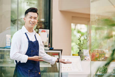 Portrait of young positive Vietnamese man welcoming clients in his cafe