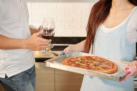 Young woman holding tray with homemade pizza when her husband carrying glasses of red wine
