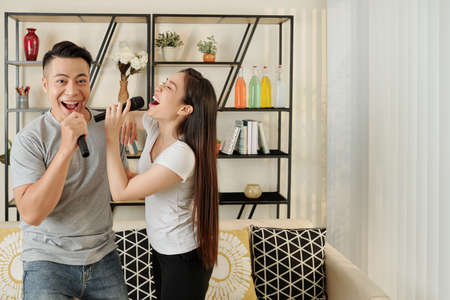 Young Vietnamese couple enjoying singing karaoke at home