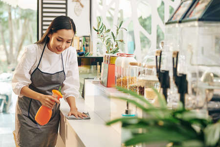 Smiling young cafe worker wiping surfaces with disinfecting detergent