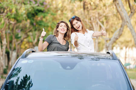 Excited pretty female friends riding in car trunk and showing thumbs-up