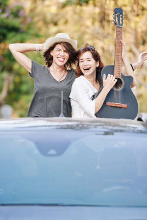 Excited happy young women riding in car trunk with guitar on summer day 写真素材