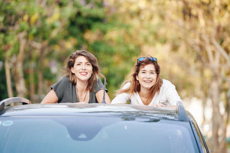 Portrait of beautiful smiling young women standing in car trunk and looking at camera