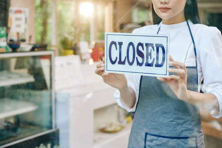 Sad female restaurant owner closing door and hanging sign