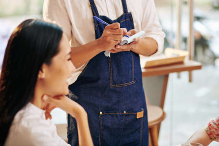 Waiter in denim apron taking order and writing it down in notebook