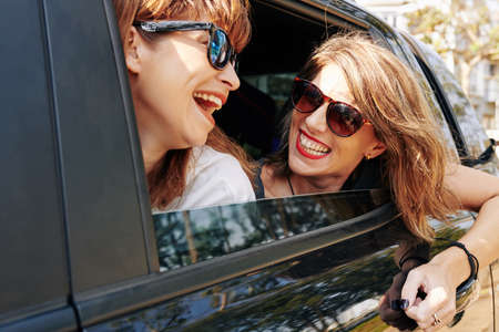 Happy excited friends in sunglasses enjoying road trip on sunny day