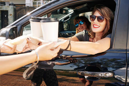Smiling pretty female driver buying take out coffee for herself and her friend