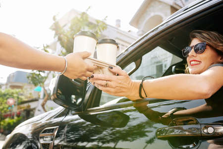 Coffeeshop worker giving cardboard tray with two cup of take-out coffee to female car driver Stok Fotoğraf