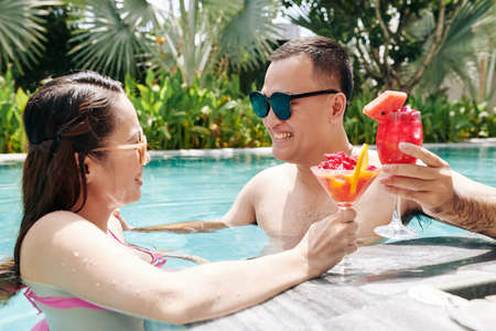Happy young Asian couple spending honemoon in swimming pool and enjoying tasty fruit smoothie