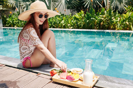 Happy pretty young Asian woman in sunglasses and straw hat sitting on edge of swimming pool and eating delicious fruits