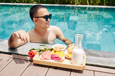 Happy young Asian woman standing in swimming pool and eating delicious breakfast