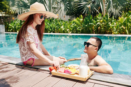Cheerful young Vietnamese couple spending sunny summer day in swimming pool and eating fresh tasty breakfast