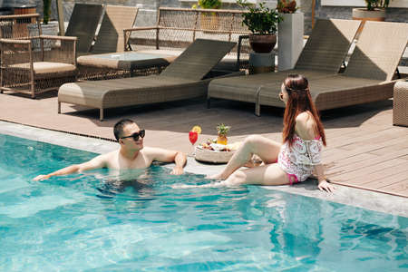 Young couple spending time in swimming pool of spa resort and eating tasty fruits