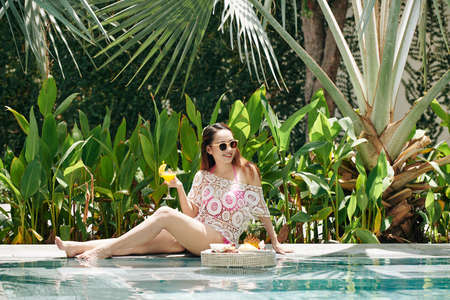Young beautiful Vietnamese woman drinking delicious fruit cocktail when resting by swimming pool