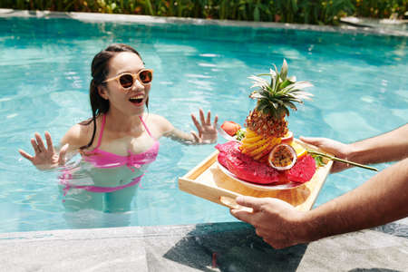 Young man bringing tray with delicious breakfast and rose flower to his excited girlfrined swimming in pool
