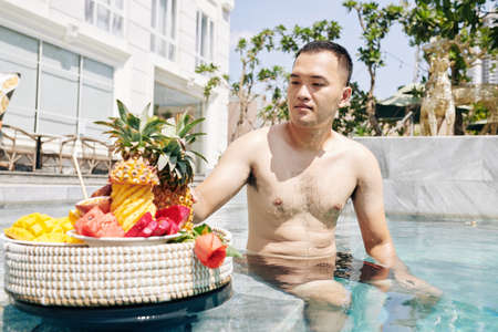 Handsome young Vietnamese man sitting on edge of swimming pool and eating tasty ripe fruits