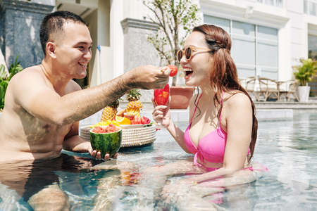 Happy young Asian man feeding his girlfriend with piece of watermelon when they are spending time in swimming pool