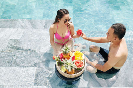 Happy young couple spending time in swimming pool and eating delicious ripe fruits, view from above Stok Fotoğraf